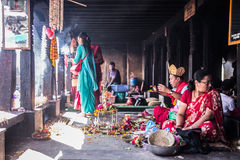 Nepal indoor ritual. Nepal - 27 October 2014 : A guy praying in small ritual ceremony with couple of believers nearby, indoor. The image shows a normal sacred Stock Photo