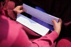 Nepal, Kathmandu, o 7 de março de 2017: Scripture da leitura da monge budista imagens de stock royalty free