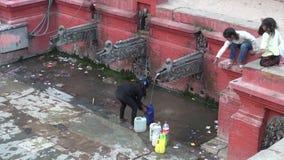 NEPAL, KATMANDU – DECEMBER 18: childrens near historical drink water-tap in Nepal capital Katmandu, December 18, 2013 stock video footage