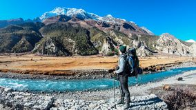 Nepal - Manag, Boy and the Yaks. A boy on the way to Manang, Annapurna Circuit Trek, Himalayas, Nepal. Young man is admiring the views. Yaks are gazing on the stock photo