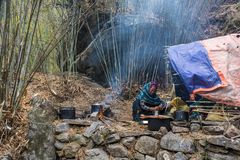 Woman preparing food around the campfire and tents on March 29,. Nepal-March 29, 2018: Woman cooking by the fire and tent on March 29, 2018, Nepal Royalty Free Stock Photography