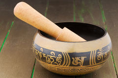 Nepal singing bowl on a wooden gold painted surface. Stock Image
