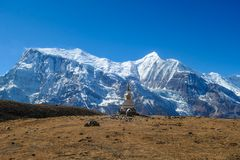 Nepal - Stupa with Annapurna Chain in the back. A stupa with Annapurna Chain as a backdrop, Annapurna Circuit Trek, Himalayas, Nepal. High mountains covered with royalty free stock photos