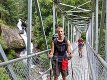 Nepal trekking. Tourist crossing bridge over cascade - Annapurna circuit trekking, Nepal royalty free stock images