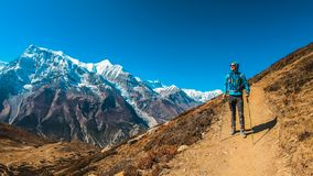 Nepal - Trekking Young Man with the view on Annapurna. Trekking Young Man wears blue, the view on Annapurna Chain, Annapurna Circuit Trek, Nepal. Way to the Ice royalty free stock photography