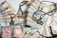 Nepal trinket with Rupee money. A hinduism charm trinket on top of a pile of Nepal Rupee bank note Stock Photos
