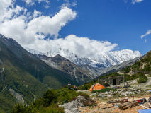 Nepal workers relaxing near Khangsar village, view to Tilicho peak, Nepal royalty free stock images