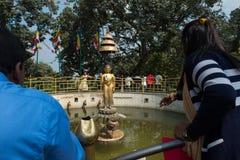 Nepalees werpt muntstuk aan het beeld van Boedha in midden van heilige vijver aan wi royalty-vrije stock afbeelding