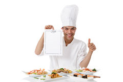 Nepalese chef menu list, thumb-up. Young attractive nepalese man chef showing menu list and thumb up. Diversity of oriental meals on plates. Studio shot, white stock images