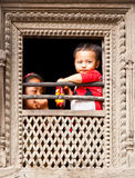 Nepalese children look from the window in Bhaktapur, Nepal. Royalty Free Stock Photography