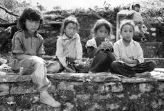 Nepalese children sitting on the wall before school Royalty Free Stock Photos