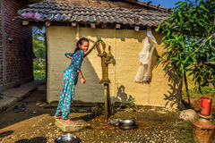 Nepalese girl gets water from a well in Nepal Royalty Free Stock Photography