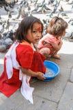 Nepalese girls feeding pigeons Royalty Free Stock Photo