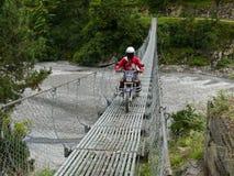 Nepalese man passing suspension bridge on motorbike Stock Photo