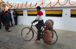Nepalese man transporting 3 gas cylinders on his bicycle at Bodnath Stupa, royalty free stock photo