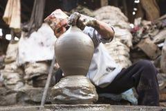 Nepalese mens die in de zijn aardewerkworkshop werken Stock Afbeeldingen