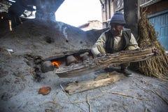 Nepalese mens die in de zijn aardewerkworkshop werken Stock Foto's