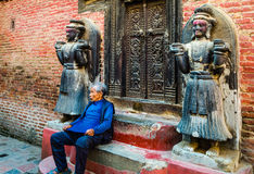 Nepalese old men sitting in front of wall located in Bhaktapur Stock Image