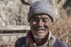 Nepalese oude mens die aan de camera lachen royalty-vrije stock afbeeldingen