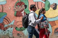 Nepalese people walking by colourful graffiti