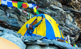 Nepalese Sherpa Mountain Climber taking Self Portrait in Tent. Nepalese Sherpa Mountain Climber taking Self Portrait on Camera of smart Phone sitting in Tent Royalty Free Stock Image