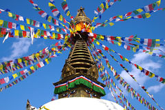 Nepalese stupa with prayer flags. On a background of the blue sky Royalty Free Stock Photography