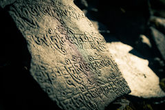 Nepalese symbols carved on the stones. Stone carved with nepalese characters and beautiful light Royalty Free Stock Image