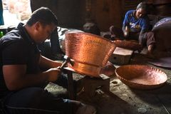 Nepalese tinmans working in the his workshop. Royalty Free Stock Image