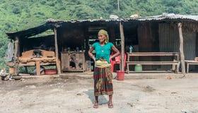 Nepalese vrouw die zich voor hut bevinden stock afbeelding