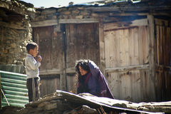 Nepalese woman and boy working near their house Stock Photography