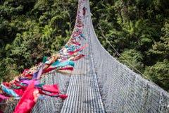 Nepalese woman crossing suspension bridge Royalty Free Stock Photos
