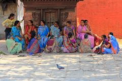 Nepalese women in their traditional Sari dress sitting in front of Taleju Temple Stock Image