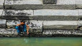 Nepalesian flicka som tvättar hennes framsida i Bagmati Arkivbilder
