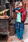 Nepalesische Frau, die vor Berg von Ganesh betet Stockbild