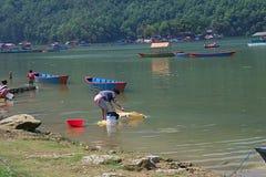 Nepalesische Frau, die Wäscherei im Phewa See tut stockfotografie