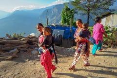 Nepalesische Frauen in der bunten Kleidung, die Kind beim Gehen außerhalb i trägt lizenzfreie stockfotografie