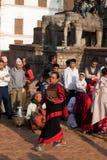 Nepalesische Frauen - Newars machen Sie ein religiöses Ritual puja - anbietendes bildhauerisches Bild der Gottheit des Lebensmitt Stockbilder