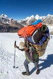 Nepalesischer Träger-tragender Korb mit Gebirgsexpeditions-Gepäck lizenzfreie stockbilder