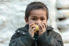 Nepalesisches Kind, das einen Apfel isst Stockfotografie