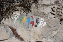 Nepalesisches religiöses Symbol, das auf einen Felsen schreibt lizenzfreie stockfotografie
