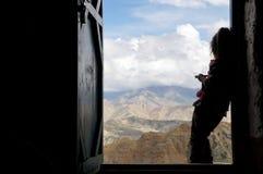 Nepalesisk girlie står mot bakgrunden av dörröppningen och ser de Himalayan bergen arkivbilder