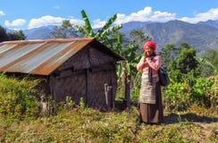 Nepalesisk kvinna i traditionell kläder som hälsar namaste bredvid hennes lilla hus royaltyfri bild