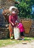 Nepalesisk kvinna och dotter med korgar på vägen, Nepal. Fotografering för Bildbyråer