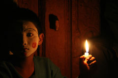 A Nepali boy in makeup holding a candle royalty free stock images