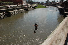 Nepali kids jumping into the river. In the Pasupatinath temple in Kathmandu, Nepal Stock Photo