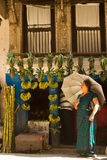 Nepali lady with umbrella outside a fruit shop, Kathmandu, Nepal Stock Photo