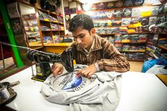Nepali man does embroidery on clothes in a small workshop. Royalty Free Stock Image