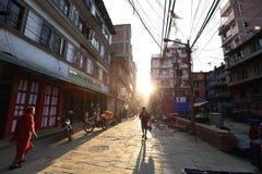 Nepali people walking down the Thamel street under sunrise in the morning in Kathmandu Royalty Free Stock Photo