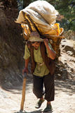 Nepali porter. Carrying 80 kgs of rice from Lukla airport to Namche Bazaar stock image