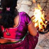 Nepalikvinnasammanträde vid en brand Arkivbild